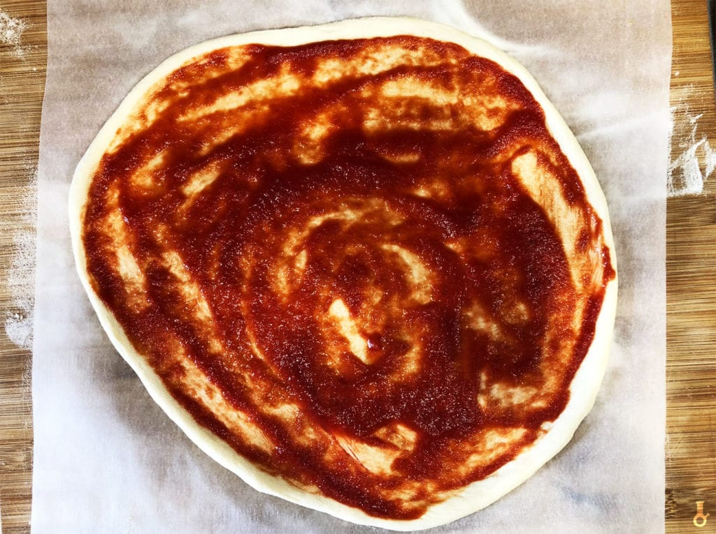 pizza posmarowana sosem